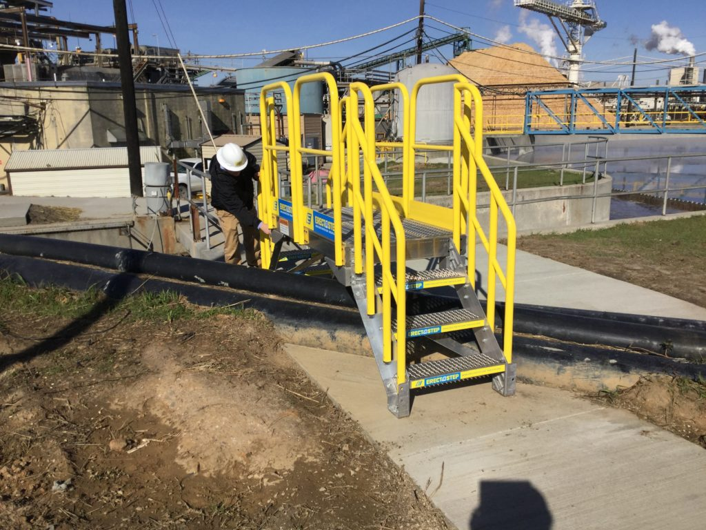 Erectastep industrial crossover stairs over outdoor pipe